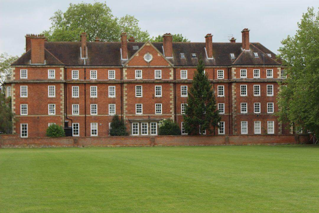 A large red brick building behind an expanse of grass field.