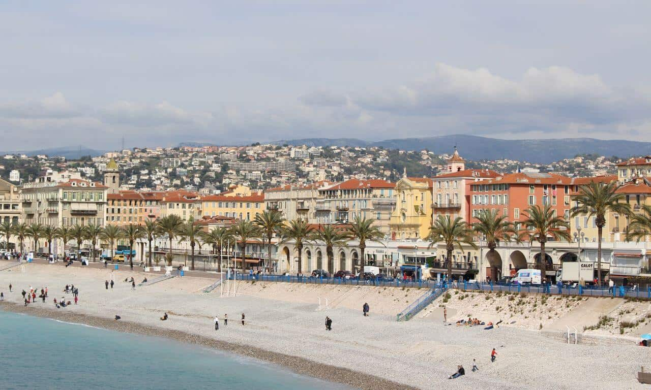 The sea, beach and Promenade des Anglais with palm trees and baroque buildings behind.