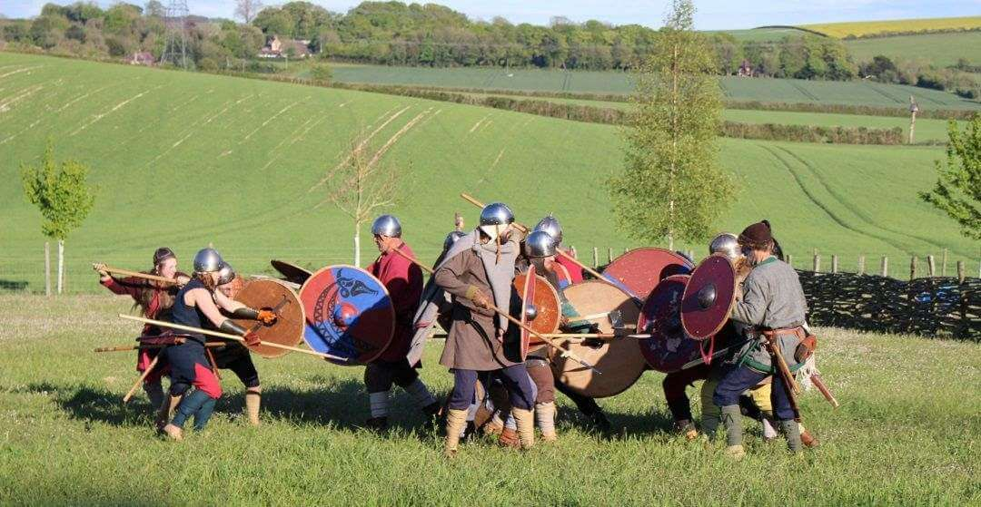 A group of people dressed as Saxons having a mock battle in a field.