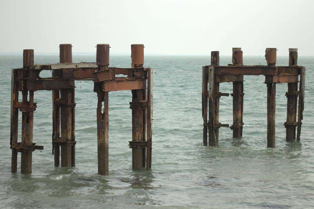 Two rusty metal structures in the sea.
