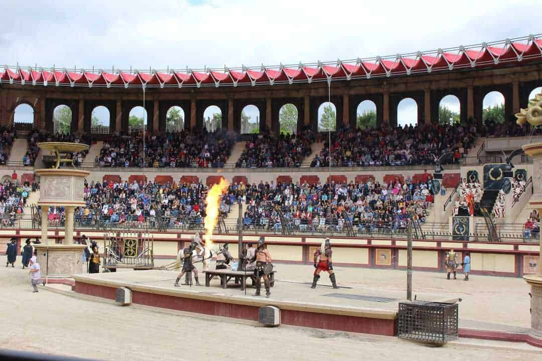 A panoramic view of the amphitheatre with gladiators and fire.