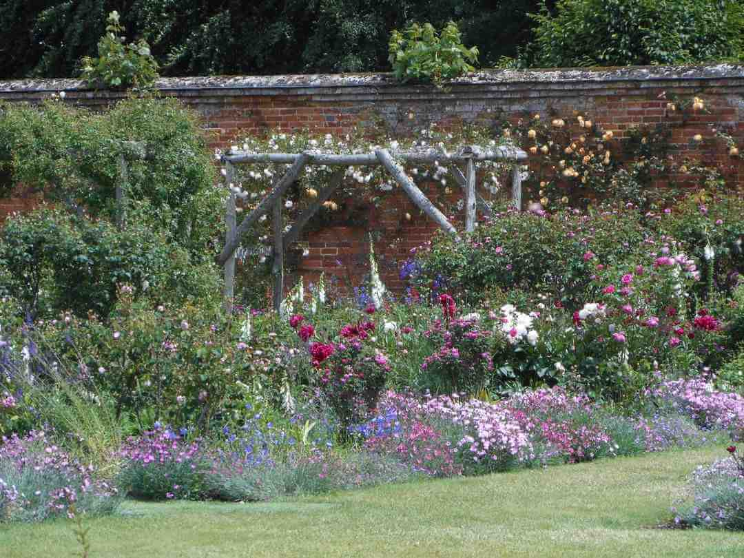 A high red brick wall covered with roses and flowerbeds full of colourful flowers.