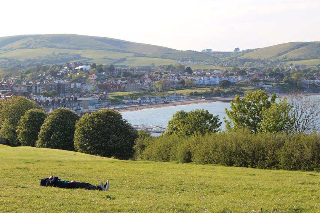 A boy lying on his back in a field at the top of a cliff overlooking a bay and a town.
