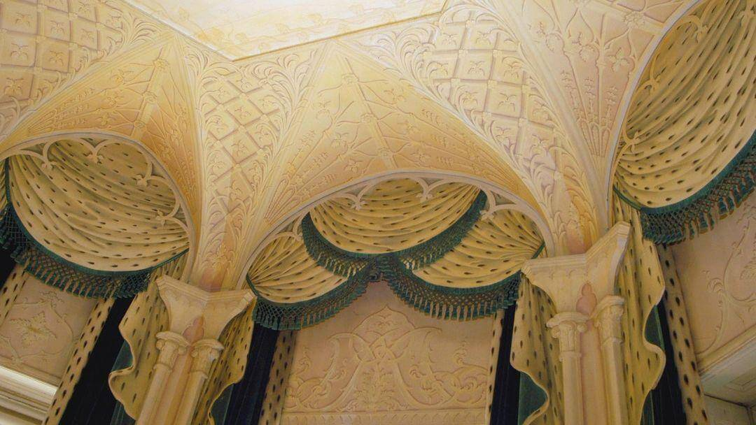A close up of a ceiling painted to look as if it has arches.