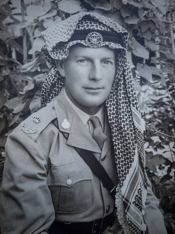 A black and white photo of a young man in soldiers uniform when in the Middle East.