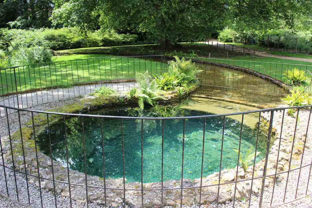 large round well lined with light grey stones and with clear blue water inside.