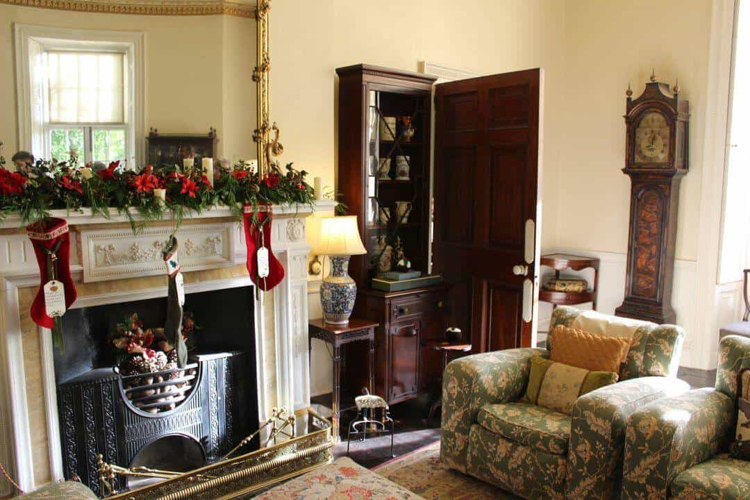 Inside a sitting room with two chairs by a fireplace decorated for Christmas.