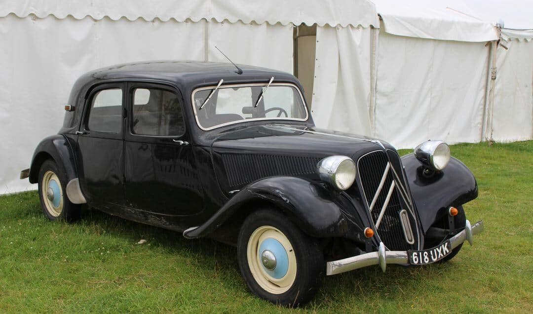 An old black citroen car parked on grass in front of a white marquee.