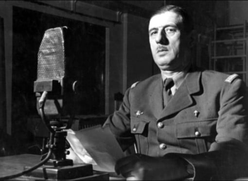 A black and white image of De Gaulle behind a microphone.