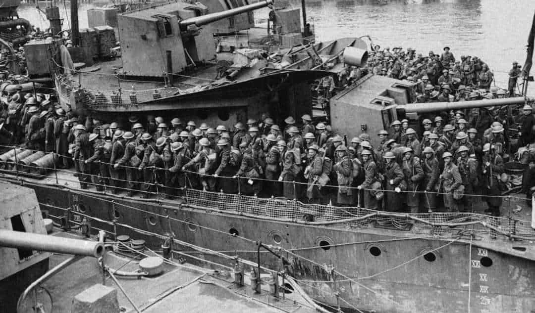 Black and white photo of rows of troops standing on deck of a ship with lots of gun turrets.