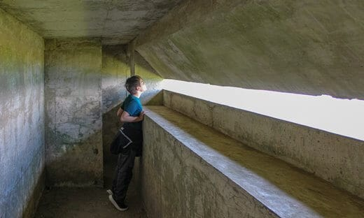 A boy standing on tiptoes looking through a narrow observation slit in a concrete bunker.