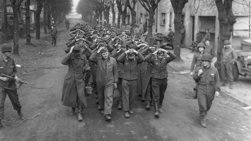 An old black and white photo of German prisoners marching with their hands on their heads.