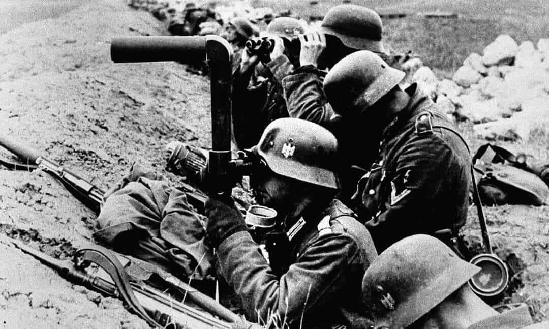 Black and white photo of German soldiers in a trench looking through a telescope.