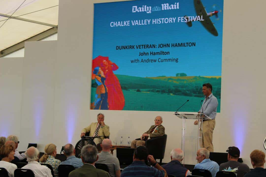 Three men on a stage with a sign behind saying John Hamilton at Chalke Valley History Festival.