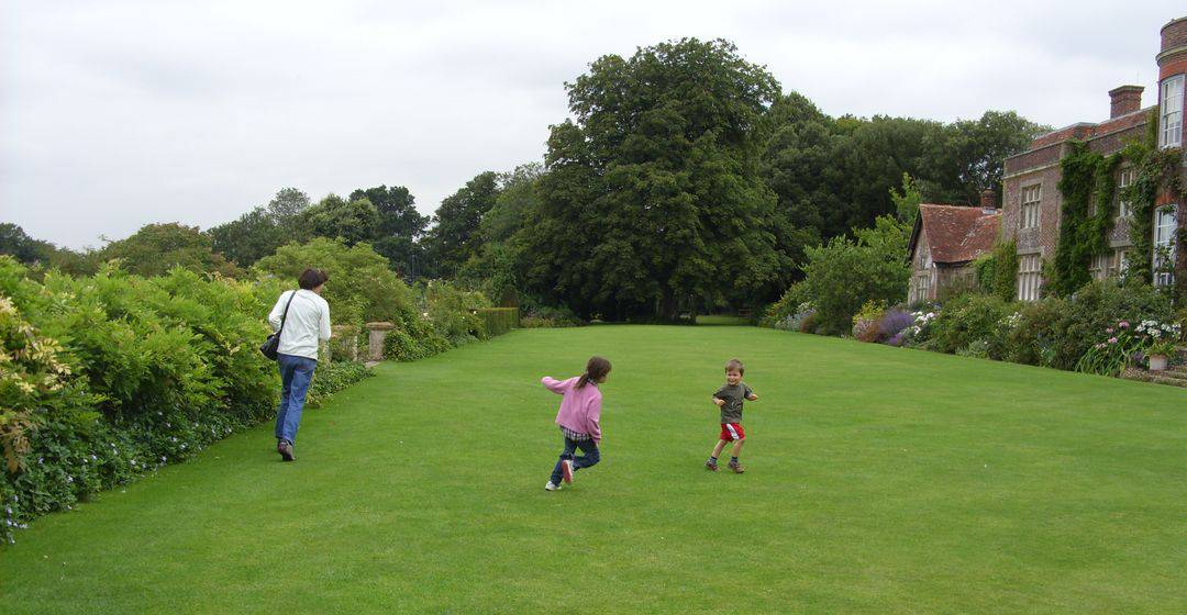 Two small children and an adult running around on lawns next to a stately home.