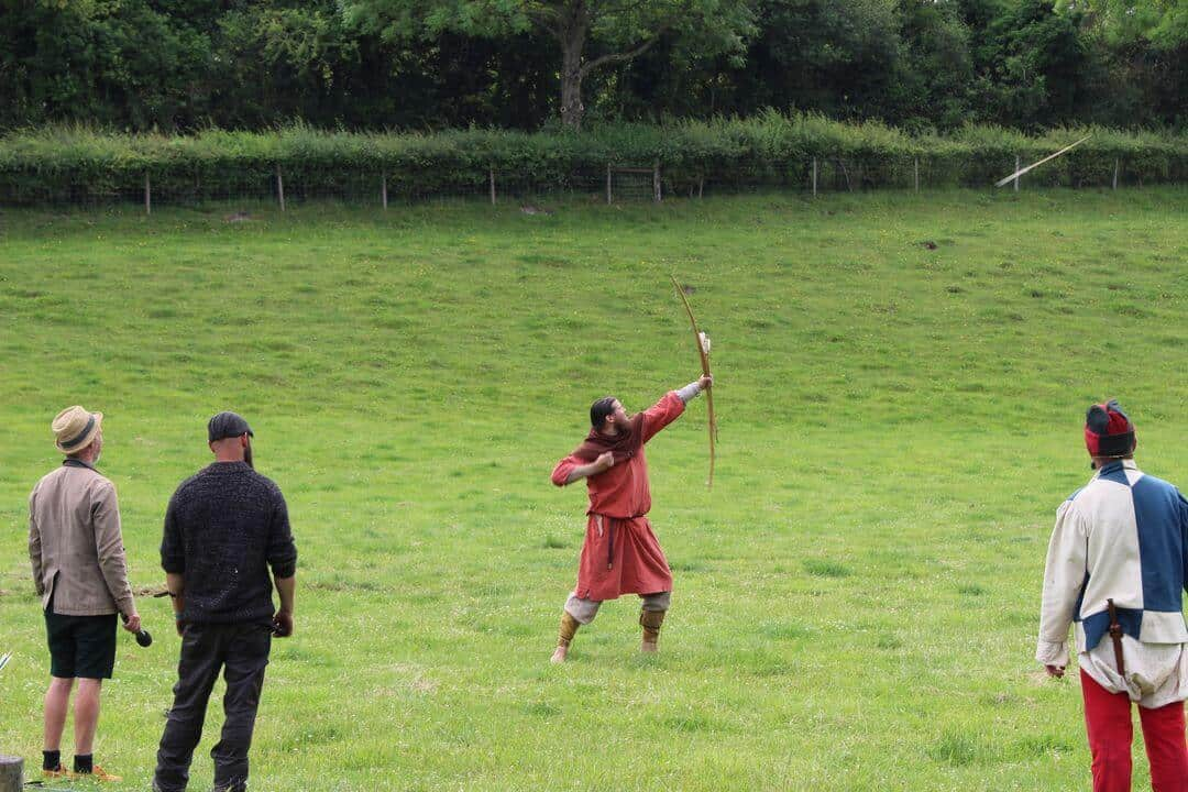 A man firing a longbow in a field watched by other men.
