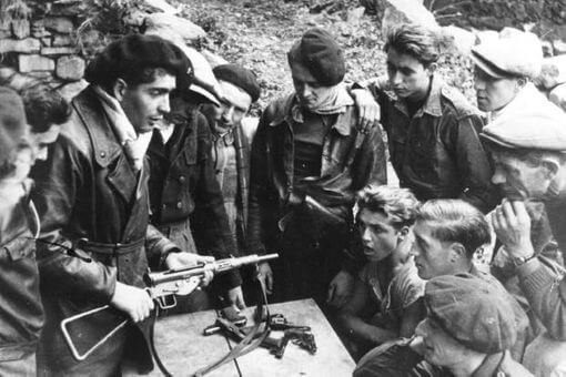 Black and white photo of men wearing berets with guns and other young men talking to them.