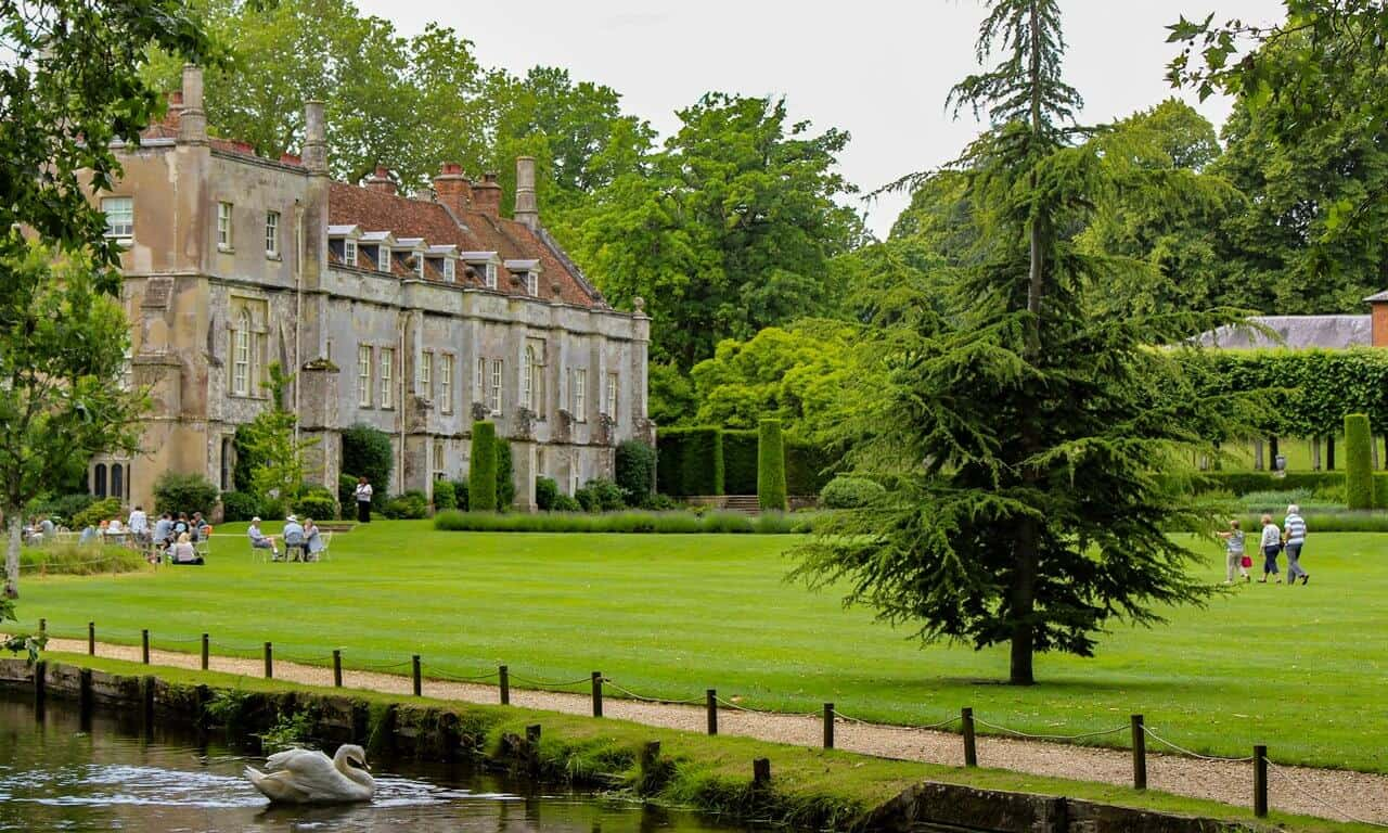 A view of Mottisfont house in the background surrounded by lawns with River Test in the foreground.