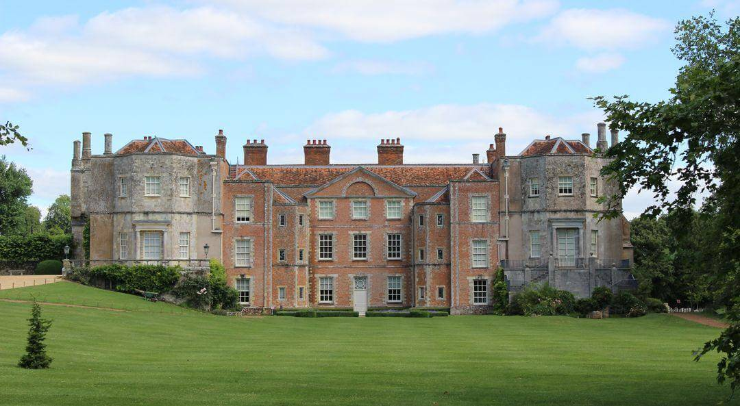 A panoramic view of Mottisfont house showing its lawns and trees on a sunny day.