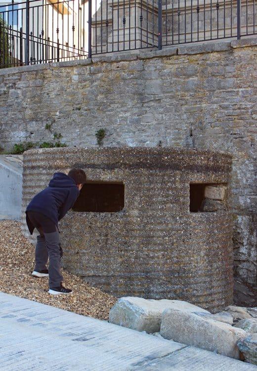A boy peering into a concrete pill box next to a wall.