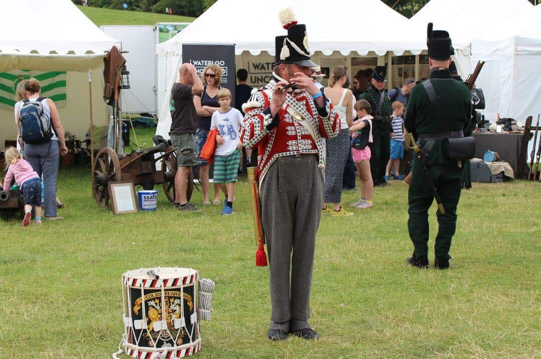 A man in 1815 soldiers uniform plays a pipe with a drum at his feet as people behind him visit a tented museum.