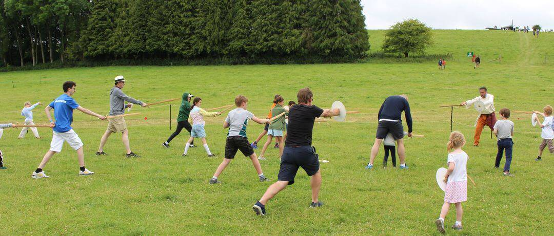 Kids and adults moving across a field holding swords with arms thrust out.