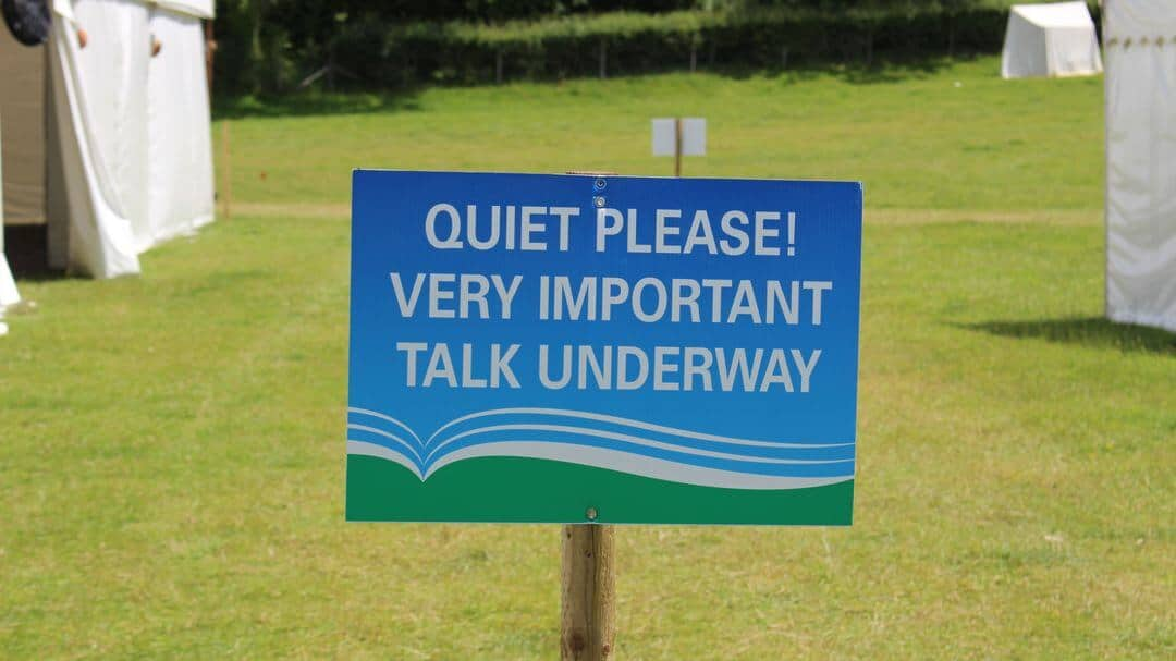A sign that says 'Quiet please very important talk underway'.
