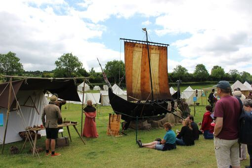 A viking longship in a field with a group of people around it listening to a talk.