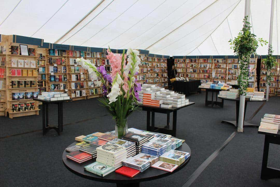 A bookshop inside a marquee with lots of bookshelves and a vase of flowers in the foreground.