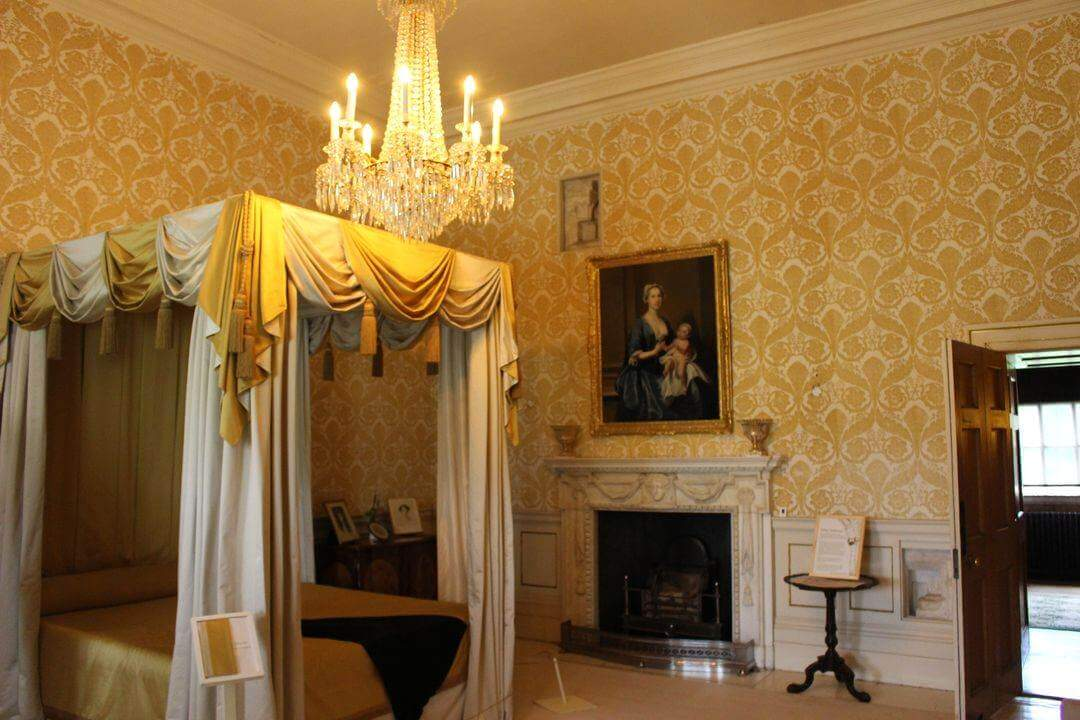 A bedroom with a four poster bed, yellow walls, a chandelier and an open door.