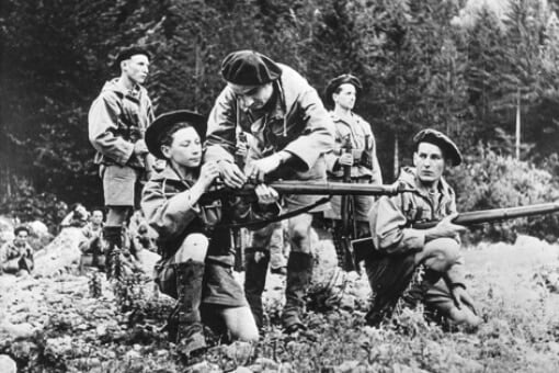 An old black and white photo of young men wearing berets with guns in a wood.