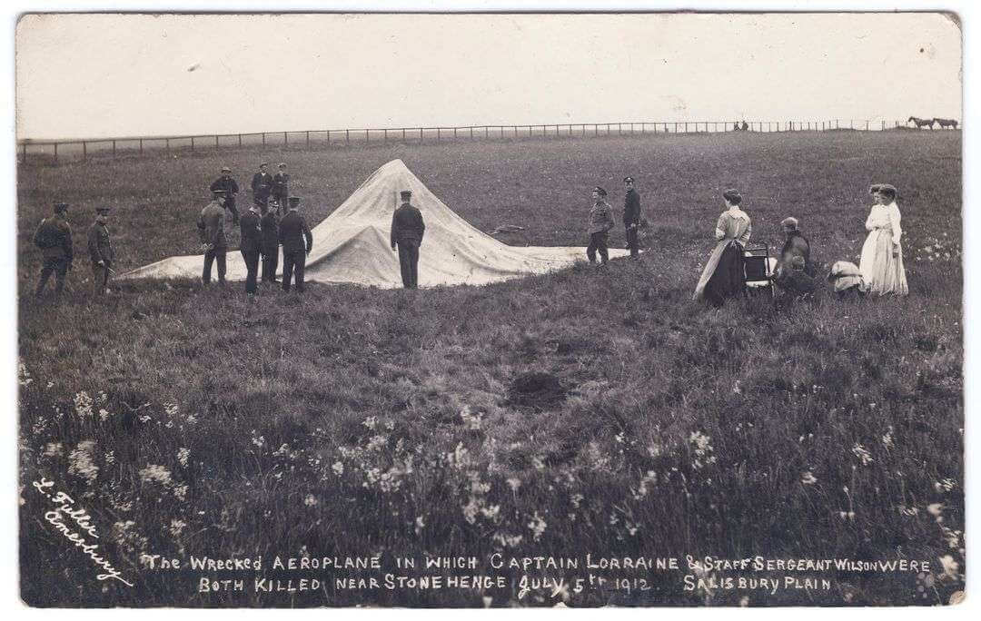 A black and white photo of a sheet covering a lump in a field with bystanders looking at it.