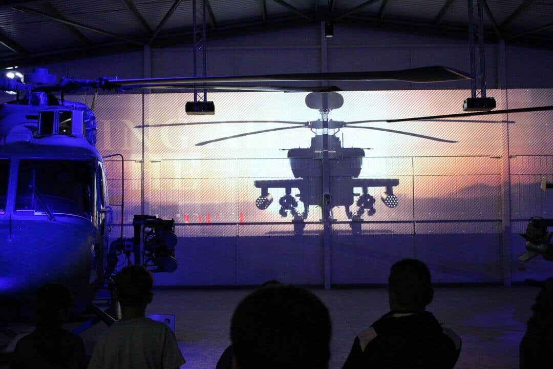 People watching a film projected onto hangar doors and a helicopter.