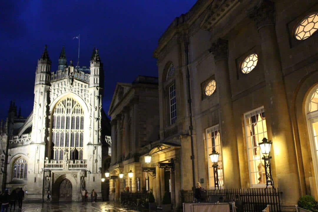 The outside of the Roman baths and Abbey lit up at night.