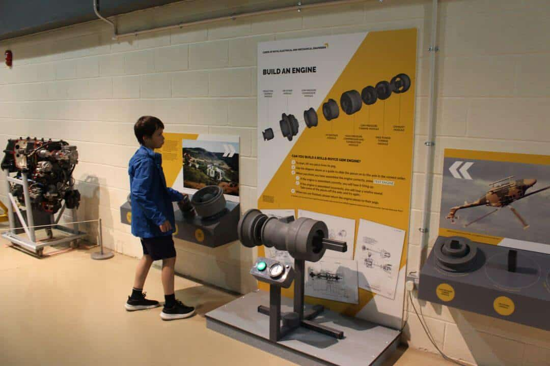 A boy standing next to a wall holding an engine part under a sign saying 'Build an Engine'.