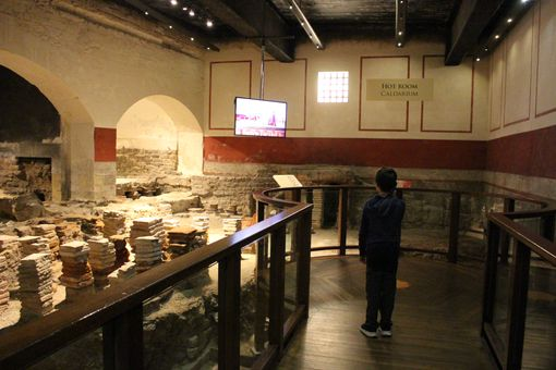 A boy on a viewing platform over a hypocaust looking at a screen.