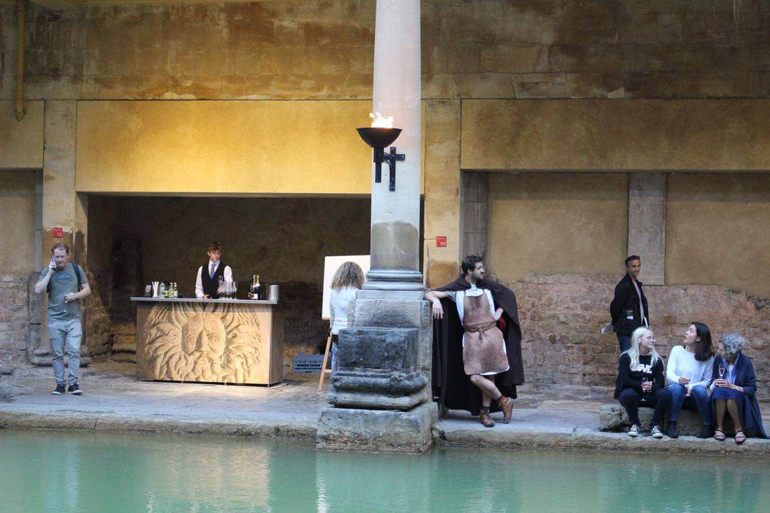 Around the edge of a green pool is a small bar and people sitting and drinking wine.