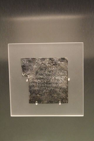 A small piece of lead inscribed with letters.