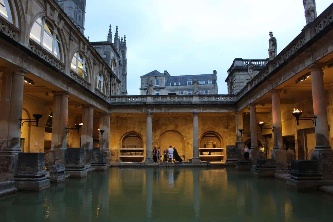 The lights reflecting on the green water of the Great Bath.