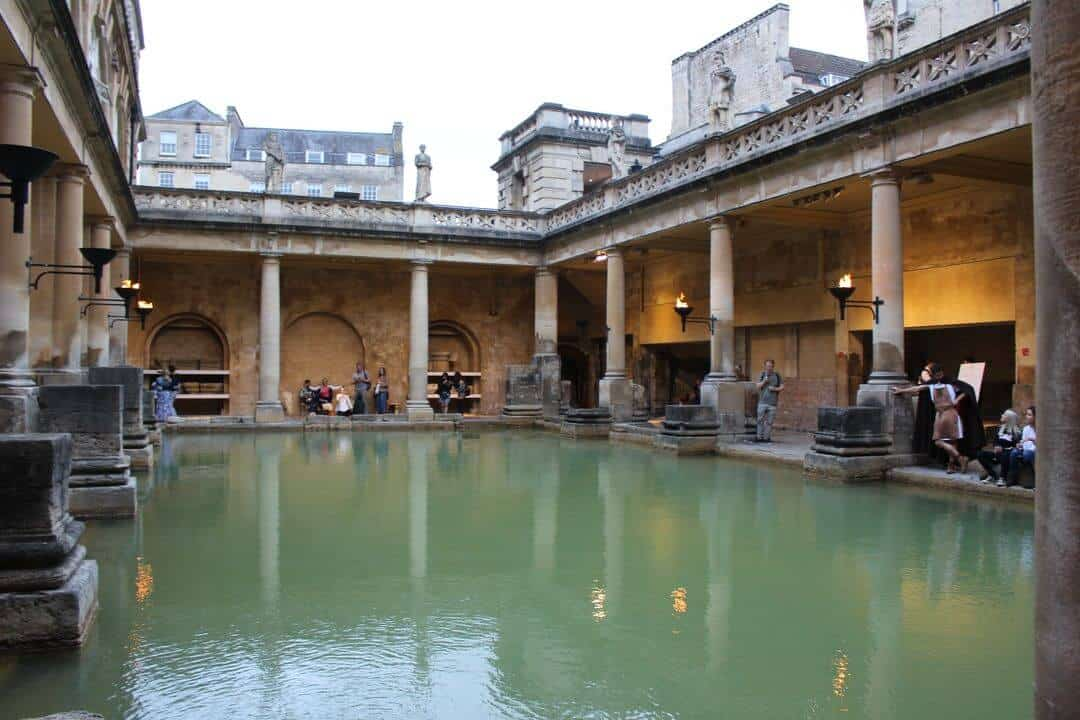 A green pool surrounded by columns wiht people around the edges.
