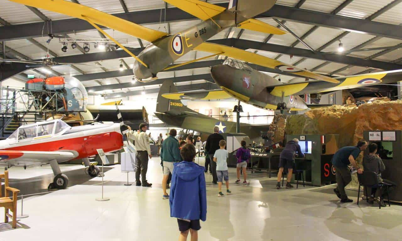 A hangar filled with aircraft and people with a boy at the front looking upwards.