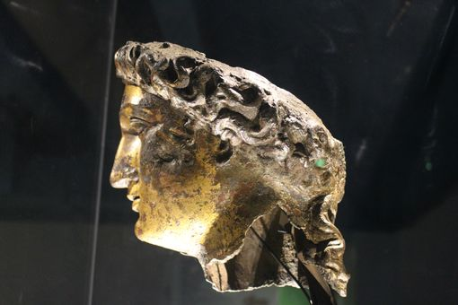 A sideways view of a gilt statue of a womans head.