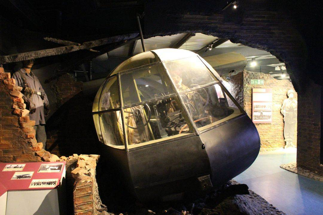 The front end of a Horsa glider in a building with a mannequin in the cockpit and one standing nearby.