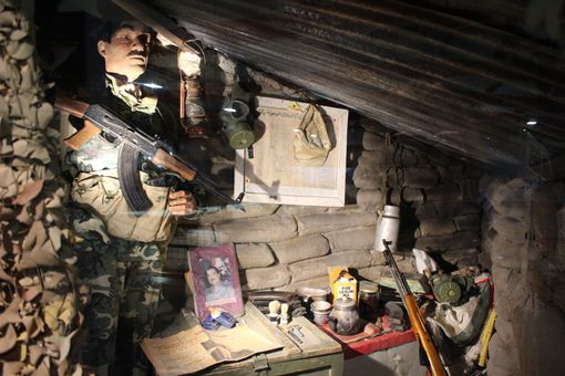 A mannequin of an Iraqi soldier in a cave holding a gun.