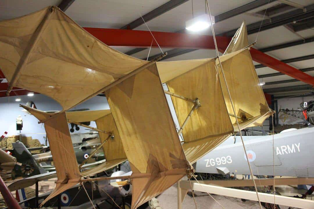 An old box kite suspended from a hangar ceiling.