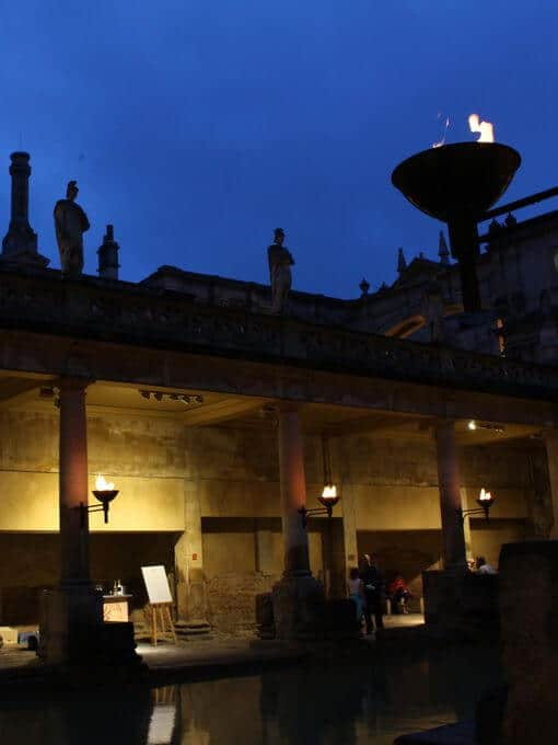 The baths at night, dark shadows and flickering torches against a dark blue sky.