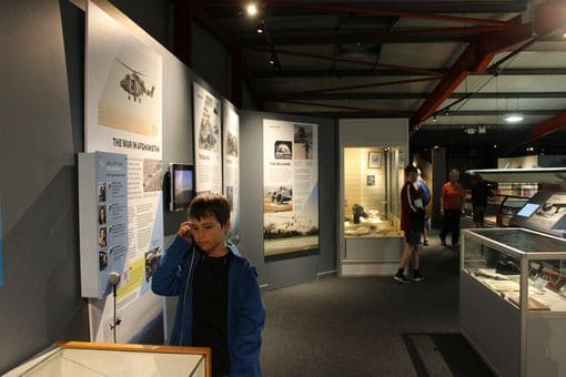 Inside a museum with a boy listening through an earpiece in front of a display.