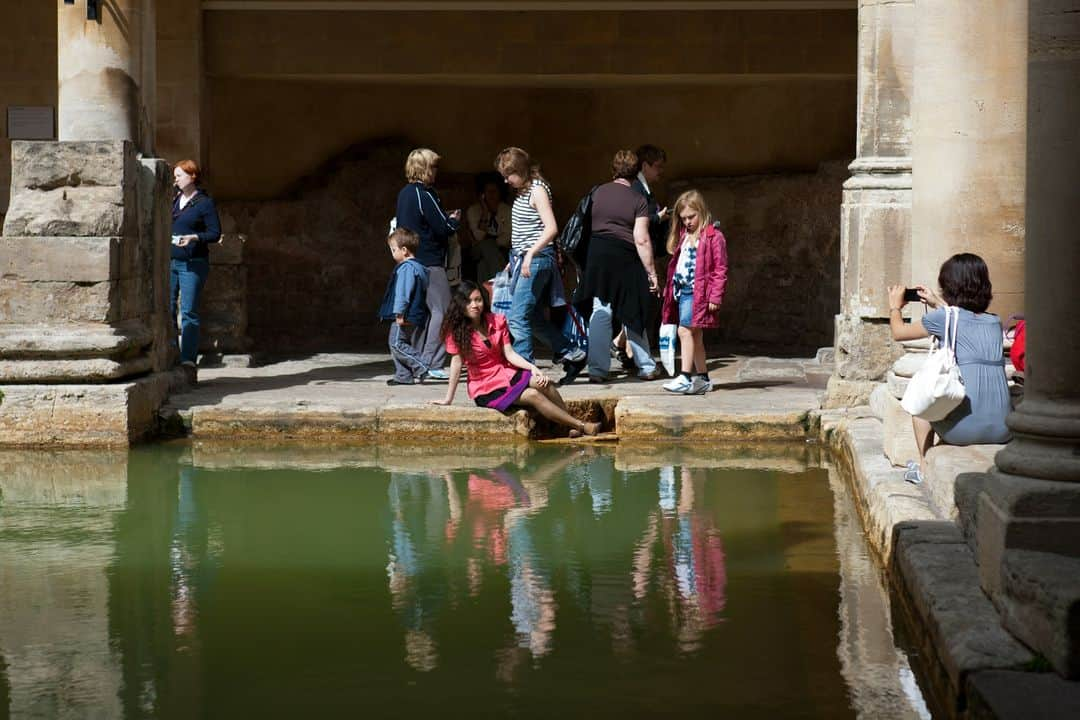 A woman taking a photo of someone posing next to the baths.