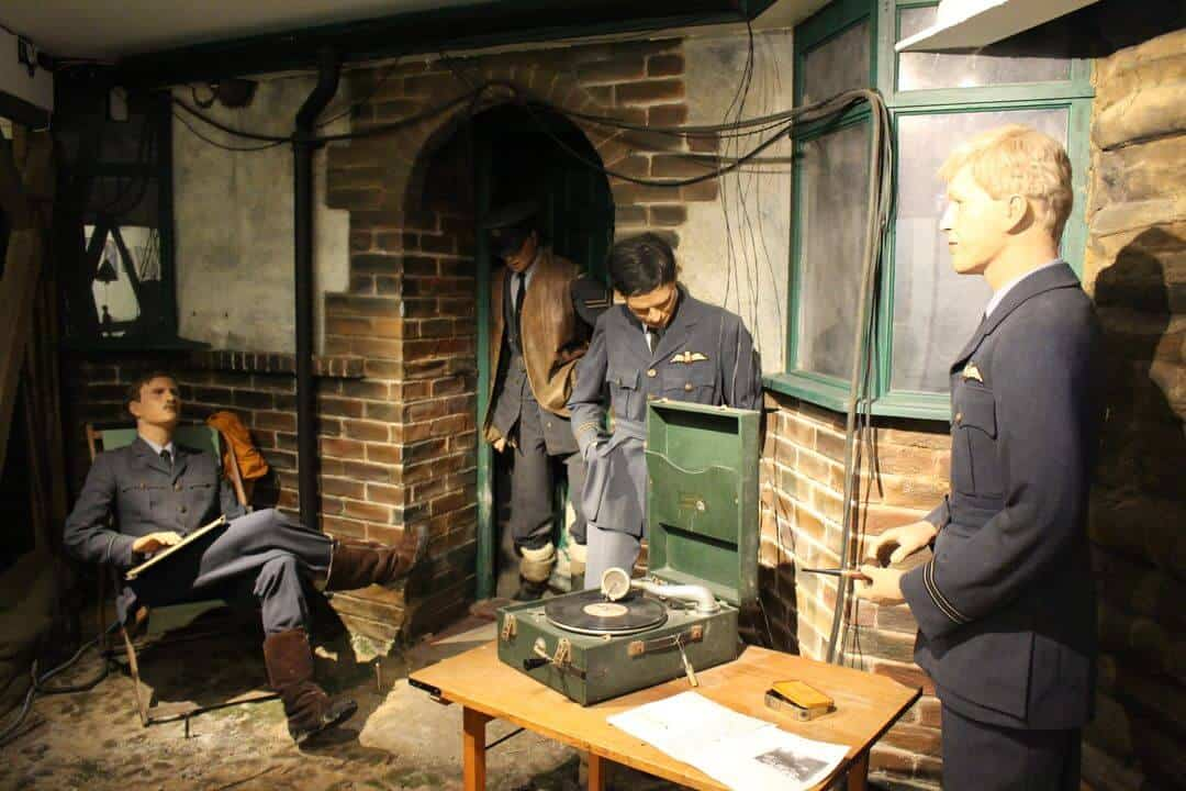 A diorama with mannequins of RAF pilots in WW2  resting and listening to a gramophone.