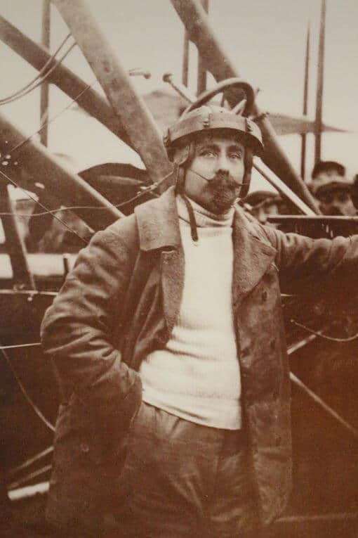 A sepia photo of a man standing in front of an old aeroplane.